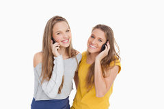 Two young women smiling on the phone Royalty Free Stock Images