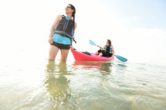 Two young women smiling in pink kayak Stock Image