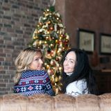 Young women smiling while sitting near Christmas tree Stock Photo