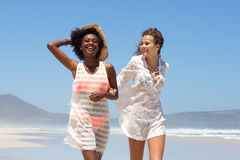 Two young women smiling and walking on the beach Royalty Free Stock Photo