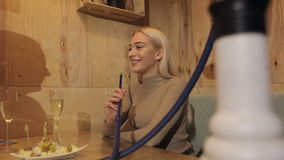 Two young women smoke hookah and drink champagne in a cafe. stock footage