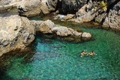 Two Young Women Snorkeling in Cinque Terre Italy. Two young women snorkeling in the brilliant green water of Manarola Italy, one of the 5 towns of Cinque Terre Royalty Free Stock Photography