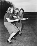 Two young women and a soldier trying out a machine gun Royalty Free Stock Photography