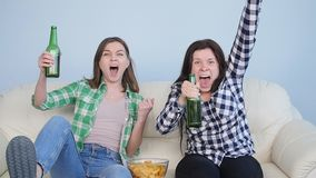 Two young women sport fans watching match. Two female sports fans watching the match at home on the couch stock footage