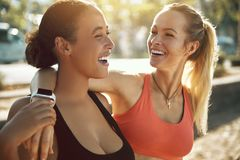 Two young women in sportswear laughing after an outdoor workout stock images