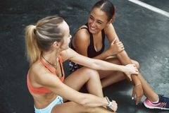 Two young women in sportswear laughing after an outdoor workout