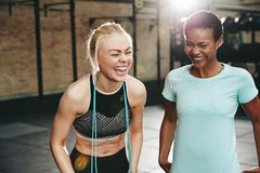 Laughing female friends standing in a gym after working out