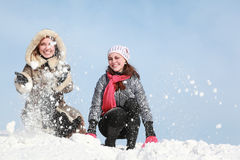 Two young women squatting and throw snow. Winter royalty free stock images