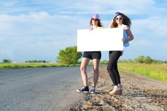 Two young women stand with a blank banner Royalty Free Stock Images