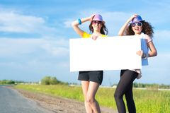 Two young women stand with a blank banner Royalty Free Stock Image