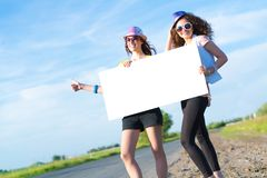 Two young women stand with a blank banner Stock Image