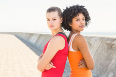Two young women standing back to back Stock Photos