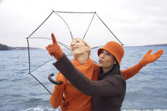 Two young women standing on the beach and pointing upwards Stock Photo