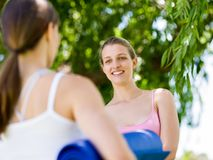Two young women with a gym mat chatting in the park Stock Photography