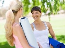 Two young women with a gym mat chatting in the park. Two young women standing and chatting with a blue gym mat in the park royalty free stock image