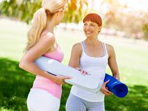 Two young women with a gym mat chatting in the park. Two young women standing and chatting with a blue gym mat in the park stock photos