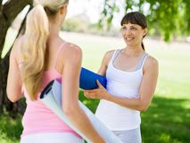Two young women with a gym mat chatting in the park Stock Photos
