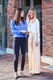 Two young women standing outside with tablet Stock Photos
