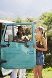 Two young women standing beside parked jeep, leaning on turquoise door, laughing, portrait Royalty Free Stock Photography