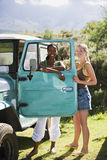 Two young women standing beside parked jeep, leaning on turquoise door, smiling, portrait Royalty Free Stock Photography