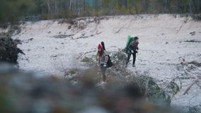 Two young women standing on a rocky road with the backpacks and guitar on the background of the forest and mountain stock video footage