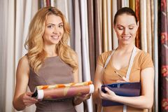 Two young women standing in store. Beautiful girl selecting tissue and smiling Royalty Free Stock Photography