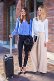Two young women standing with suitcase Royalty Free Stock Photos
