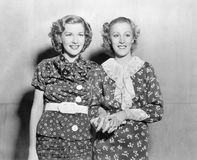 Two young women standing together and holding hands Stock Photos