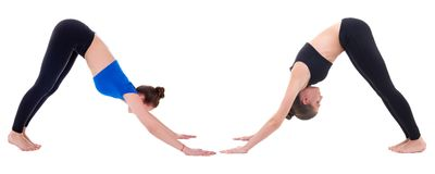 Two young women standing in yoga pose isolated on white Stock Photos