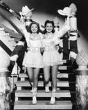 Two young women stepping down a staircase waving their western hats Royalty Free Stock Photo