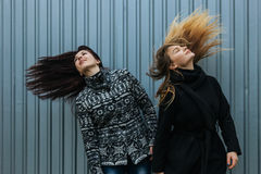 Two young women with straight long hairs in motion Stock Photo