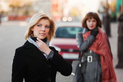 Two young fashion women walking on a city street Royalty Free Stock Photography