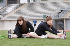 Two young women stretching in a sports stadium. Royalty Free Stock Photo
