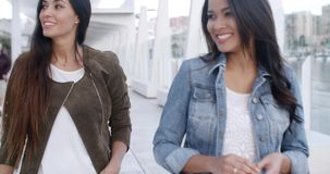 Two young women strolling down a promenade stock footage