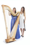 Two young women in studio with harp and clarinet against white b Stock Images