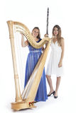 Two young women in studio with harp and clarinet against white b Royalty Free Stock Images