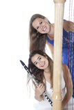 Two young women in studio with harp and clarinet against white b Stock Photo