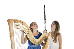 Two young women in studio with harp and clarinet against white b Stock Photography