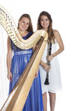 Two young women in studio with harp and clarinet against white b Stock Image