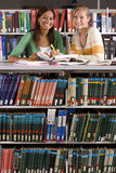 Two young women studying in library, smiling, portrait Royalty Free Stock Images