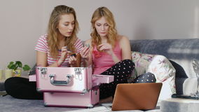 Two young women studying new makeup samples at home. Pajama party girlfriends stock footage