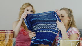 Two young women are studying their purchases. Get clothes out of the bags and watch. Successful Shopping. After a successful shopping. Two women looking at their stock footage