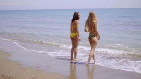 Two young women in swimsuits standing in the sea stock footage