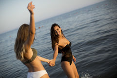 Two young women in swimwear having fun. In the sea at sunset Stock Photography