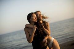 Two young women in swimwear having fun in the sea. At sunset Stock Photos