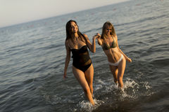 Two young women in swimwear having fun. In the sea at sunset Royalty Free Stock Photo