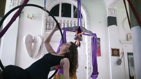 Two young women swinging on a hoop and making gymnastic elements on aerial silk. Slow motion stock video footage