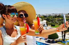 Two young women taking picture of themselves on vacation.  Stock Photography