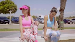 Two young women taking a rest from a workout. Two attractive sporty young women taking a rest from a workout sitting on a wall in the sunshine staring off to the stock video