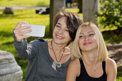 Two young women taking self photos with phone outside. Royalty Free Stock Photo